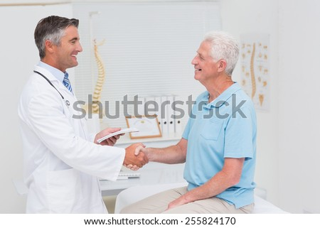 Side view of male doctor and senior patient shaking hands in clinic - stock photo