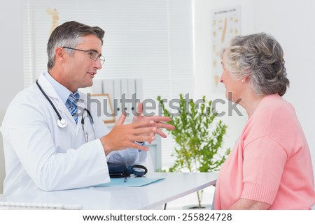 Side view of male doctor conversing with female patient at table in clinic - stock photo