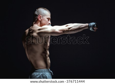 side view of male fighter makes punch on black background - stock photo