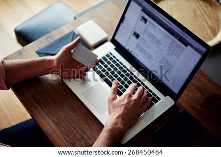 Side view of male hands holding credit card and typing text on laptop at office sitting at the wooden table, on-line shopping at home, cross process, filtered image - stock photo