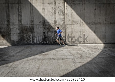 Side view of male runner with blue shirt and smart watch, who runs under concrete arcades.