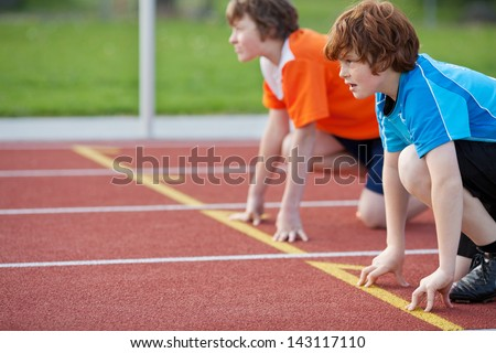 Side view of male runners on starting position at racetrack - stock photo