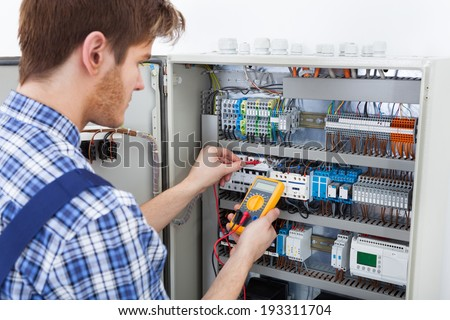 Side view of male technician examining fusebox with digital insulation resistance tester