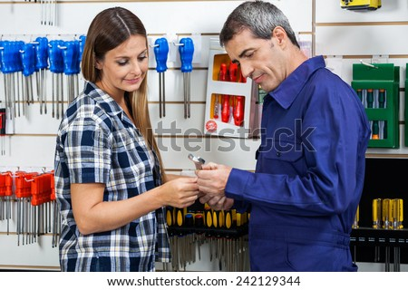 Side view of male vendor showing wrench to female customer in hardware shop - stock photo
