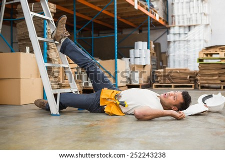 Side view of male worker lying on the floor in warehouse - stock photo