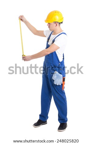 side view of man builder in blue coveralls holding measure tape isolated on white background - stock photo