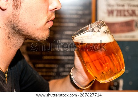 Side view of man drinking large beer