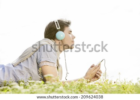 Side view of man enjoying music on MP3 player using headphones in park against clear sky - stock photo