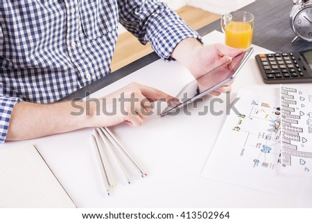 Side view of man in casual shirt using pad at office desk with business sketch, calculator and orange juice and pencils