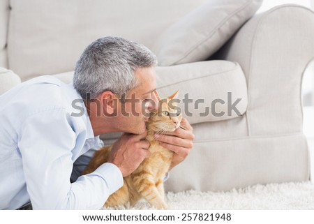 Side view of man kissing cat by sofa at home - stock photo