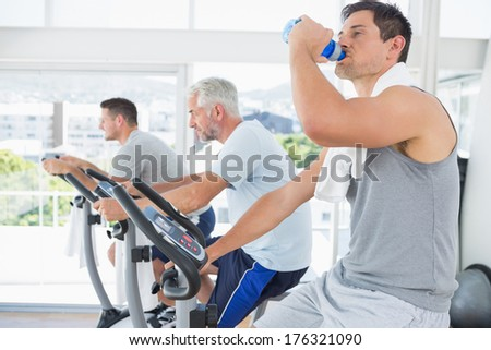 Side view of man on exercise bike drinking water at fitness studio - stock photo