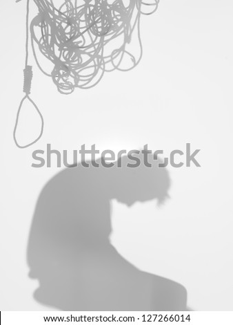 side view of man sitting with a tangled hanging rope on top of his head, behind a diffuse surface - stock photo