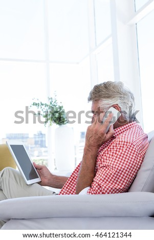Side view of man talking on phone while holding digital tablet at home