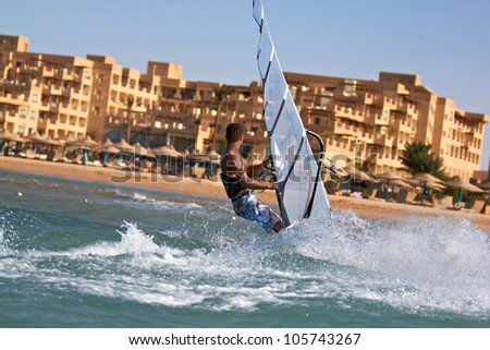 Side view of man windsurfing in splashes of water