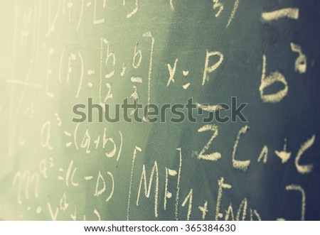 side view of math formulas and calculation written over chalkboard. selective focus.  - stock photo