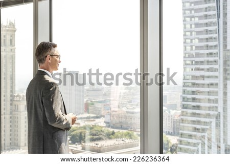 Side view of mature businessman looking through office window - stock photo