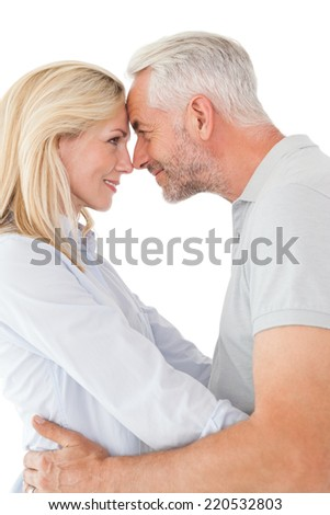 Side view of mature couple looking at each other over white background