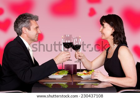 Side view of mature couple toasting wineglasses at table in restaurant - stock photo