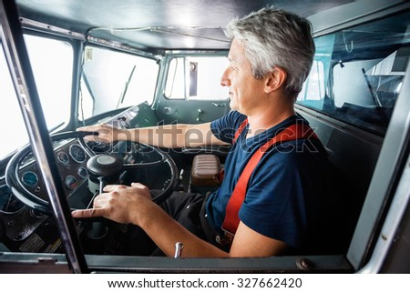 Side view of mature fireman driving firetruck at station - stock photo