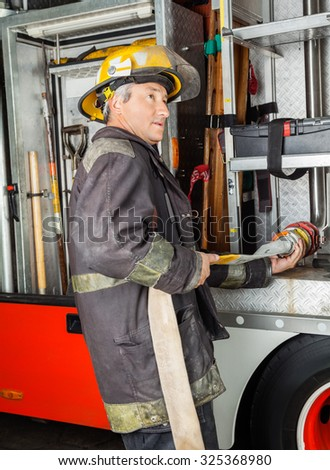 Side view of mature fireman fixing water hose in truck at fire station