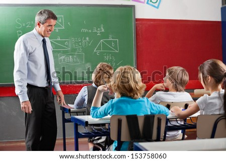 Side view of mature male teacher looking at students sitting in classroom - stock photo