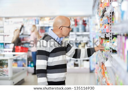 Side view of mature man shopping in a supermarket - stock photo
