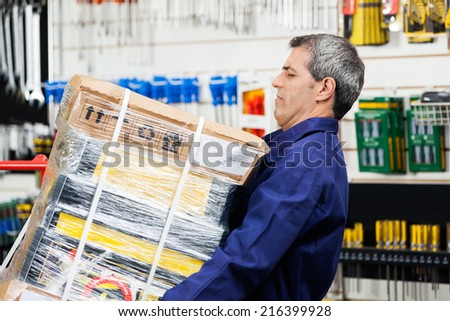 Side view of mature worker lifting heavy tool package in hardware shop - stock photo