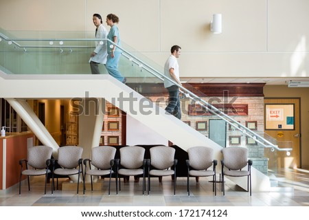 Side view of medical team and man using staircase in hospital - stock photo