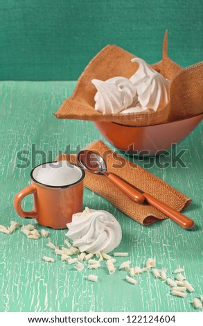 Side view of meringue, orange mug with milk foam, two spoons on textile napkin on green cracked background - stock photo