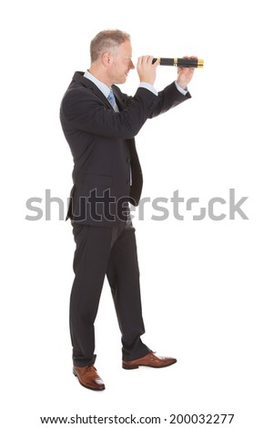 Side view of mid adult businessman looking through handheld telescope over white background