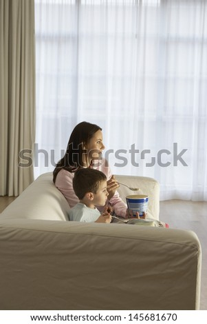 Side view of mother and son watching television while eating icecream at home