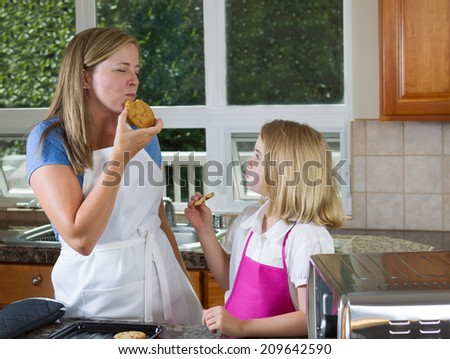Side view of mother, eyes closed, eating her freshly baked cookie with her young daughter watching her enjoy the moment - stock photo