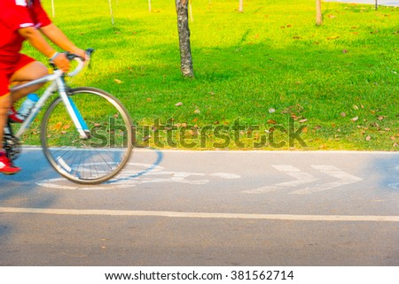 Side view of motion blurred bicyclist in bike lane. - stock photo