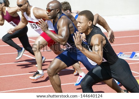 Side view of multiethnic male athletics sprinting on running track - stock photo