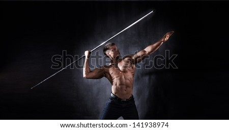 Side view of muscular bodybuilder with bare chest throwing javelin, studio background. - stock photo
