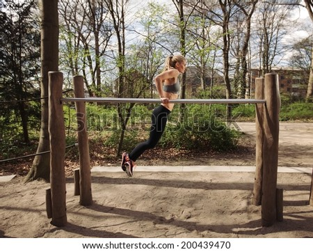 Side view of muscular young woman doing triceps dips on parallel bars at park. Caucasian female fitness model exercising outdoors. - stock photo