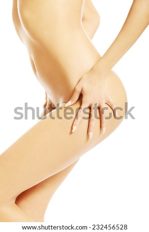 Side view of naked woman body, touching her thigh. - stock photo
