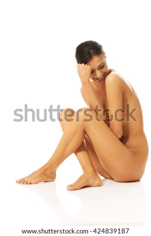 Side view of nude woman laughing and looking down