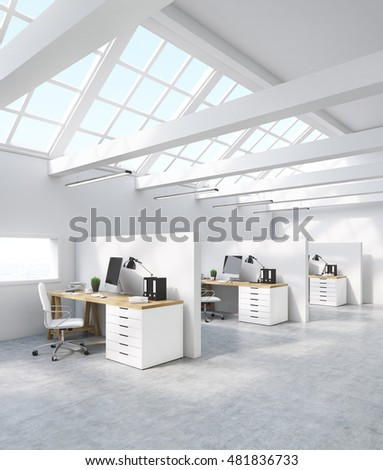 Side view of office cubicles with computer screen, binders, tables and  windows in roof