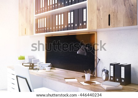 Side view of office workplace with wooden desk, drawers, shelves with documents and small blank chalkboard on concrete background. Toned image. Mock up, 3D Rendering