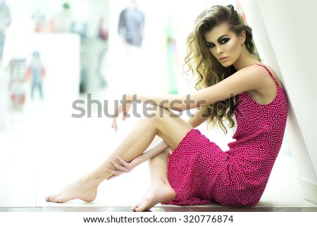 Side view of one beautiful straight young blonde woman model with bright makeup and curly hair in red dress sitting barefoot on stairs in shop on light background, horizontal picture - stock photo