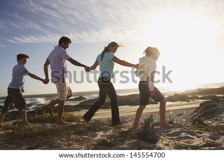 Side view of parents and children walking hand in hand on beach - stock photo