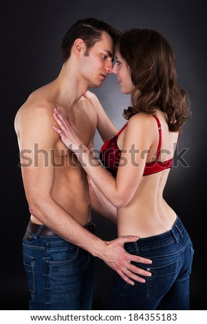Side view of passionate young couple standing isolated over black background