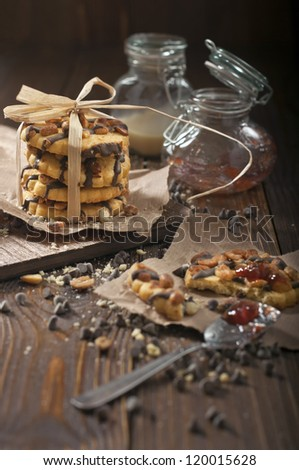 Side view of peanut biscuits, chocolate drops and jars with jam and condensed milk made in the dark tonality - stock photo