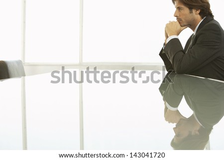 Side view of pensive businessman sitting at conference table - stock photo