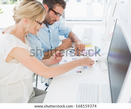 Side view of photo editors working on computers in a bright office - stock photo