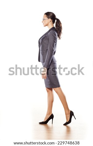 Side view of pretty business woman standing on white background - stock photo