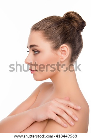 Side view of pretty woman touching her shoulder on white background - stock photo
