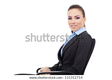 side view of pretty young business woman sitting on an office chair and smiling at the camera - stock photo