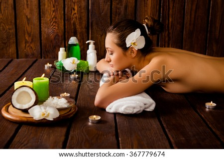 Side view of pretty young woman laying in spa salon with closed eyes and relaxed - stock photo